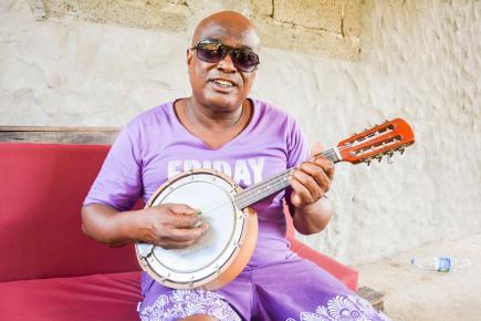Le chanteur fredonnant  un air avec  sa banjoline.