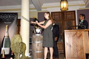 Aurélie Vythee, épouse d'Iven Vythee, s'initiant au sabrage du champagne.