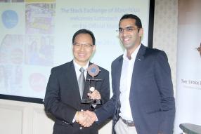 Vikash Tulsidas, membre du conseil d'administration de la Stock Exchange of Mauritius, remettant un trophée symbolique à Cyril How Kin Sang, Chairman du Listing Committee du Lottotech, pour l'occasion.